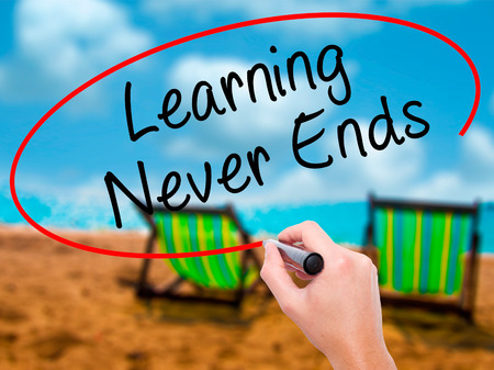 Man Hand writing Learning Never Ends with black marker on visual screen. Isolated on sunbed on the beach. Business, technology, internet concept. Stock Photo Stock Photo