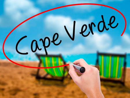 Man Hand writing Cape Verde with black marker on visual screen. Isolated on sunbed on the beach. Business, technology, internet concept. Stock Photo Stock Photo