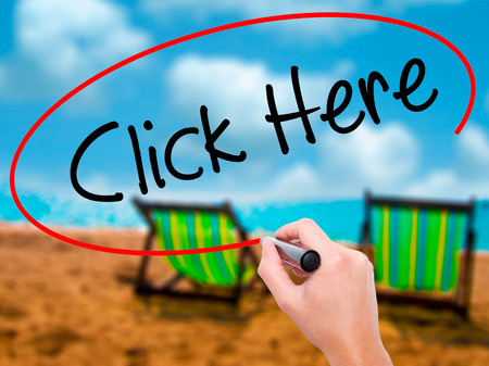 Man Hand writing Click Here with black marker on visual screen. Isolated on sunbed on the beach. Business, technology, internet concept. Stock Photo
