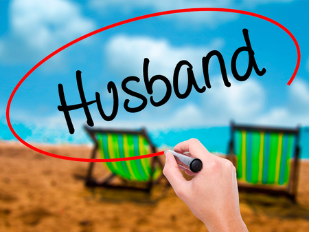 Man Hand writing Husband with black marker on visual screen. Isolated on sunbed on the beach. Business, technology, internet concept. Stock Photo Stock Photo