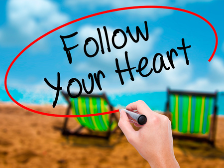 Man Hand writing Follow Your Heart with black marker on visual screen. Isolated on sunbed on the beach. Business, technology, internet concept. Stock Photo Stock Photo