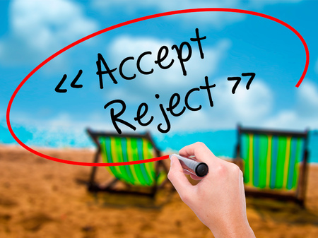 approvement: Man Hand writing Accept - Reject  with black marker on visual screen. Isolated on sunbed on the beach. Business, technology, internet concept. Stock Photo