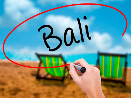 bali province: Man Hand writing Bali  with black marker on visual screen. Isolated on sunbed on the beach. Business, technology, internet concept. Stock Photo