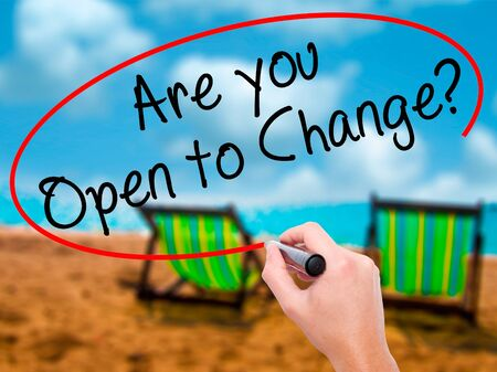 Man Hand writing Are you Open to Change? with black marker on visual screen. Isolated on sunbed on the beach. Business, technology, internet concept. Stock Photo