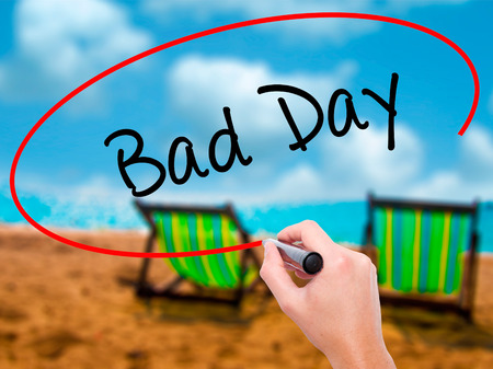 Man Hand writing Bad Day  with black marker on visual screen. Isolated on sunbed on the beach. Business, technology, internet concept. Stock Photo