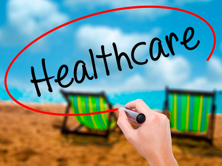 Man Hand writing Healthcare with black marker on visual screen. Isolated on sunbed on the beach. Business, technology, internet concept. Stock Photo