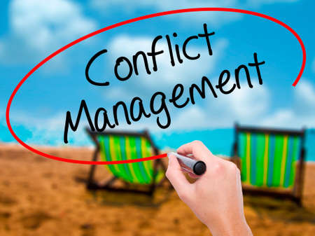Man Hand writing Conflict Management with black marker on visual screen. Isolated on sunbed on the beach. Business, technology, internet concept. Stock Photo Stock Photo