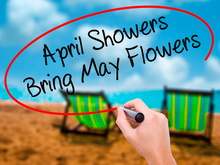 Man Hand writing April Showers Bring May Flowers with black marker on visual screen. Isolated on sunbed on the beach. Business, technology, internet concept. Stock Photo