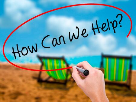 can we help: Man Hand writing How Can We Help? with black marker on visual screen. Isolated on sunbed on the beach. Business, technology, internet concept. Stock Photo