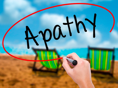 apathy: Man Hand writing Apathy  with black marker on visual screen. Isolated on sunbed on the beach. Business, technology, internet concept. Stock Photo