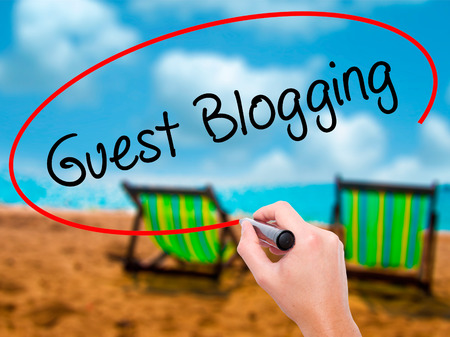 optimizer: Man Hand writing Guest Blogging  with black marker on visual screen. Isolated on sunbed on the beach. Business, technology, internet concept. Stock Photo