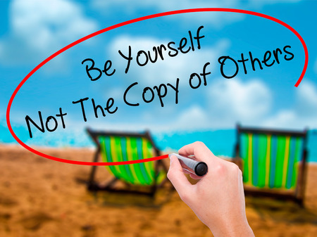 Man Hand writing Be Yourself Not The Copy of Others with black marker on visual screen. Isolated on sunbed on the beach. Business, technology, internet concept. Stock Photo Stock Photo