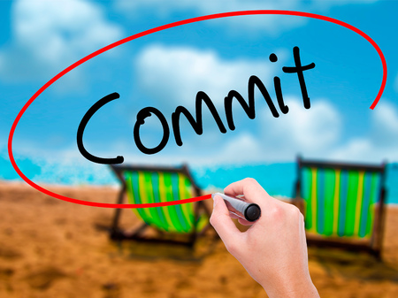 comit� d entreprise: Man Hand writing Commit with black marker on visual screen. Isolated on sunbed on the beach. Business, technology, internet concept. Stock Photo Banque d'images