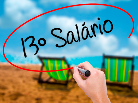 Man Hand writing 13 Salary (13o salario In Portuguese)  with black marker on visual screen. Isolated on sunbed on the beach. Business, technology, internet concept. Stock Photo