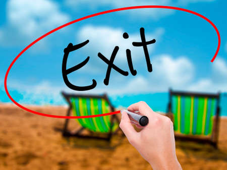downsize: Man Hand writing Exit with black marker on visual screen. Isolated on sunbed on the beach. Business, technology, internet concept. Stock Photo