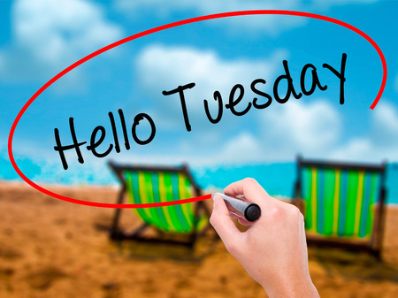 Man Hand writing Hello Tuesday with black marker on visual screen. Isolated on sunbed on the beach. Business, technology, internet concept. Stock Photo