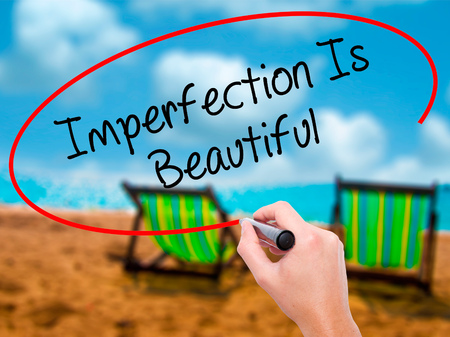Man Hand writing Imperfection Is Beautiful with black marker on visual screen. Isolated on sunbed on the beach. Business, technology, internet concept. Stock Photo Stock Photo