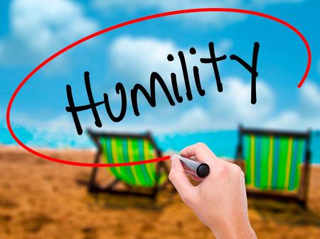 humildad: Hombre de la mano escribiendo Humildad con marcador negro en la pantalla visual. Aislado en el ba�o de sol en la playa. Negocios, la tecnolog�a, el concepto de internet. Foto de stock