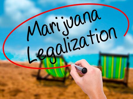 Man Hand writing Marijuana Legalization with black marker on visual screen. Isolated on sunbed on the beach. Live, technology, internet concept. Stock Photo Stock Photo