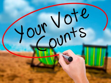 Man Hand writing Your Vote Counts with black marker on visual screen. Isolated on sunbed on the beach. Business, technology, internet concept. Stock Image Stock Photo