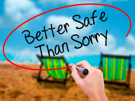 better safe than sorry: Man Hand writing Better Safe Than Sorry with black marker on visual screen. Isolated on sunbed on the beach. Business, technology, internet concept. Stock Photo