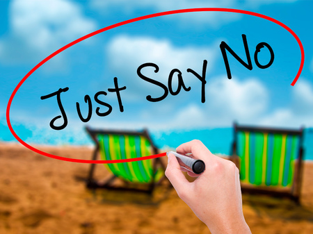 Man Hand writing Just Say No with black marker on visual screen. Isolated on sunbed on the beach. Business, technology, internet concept. Stock Photo