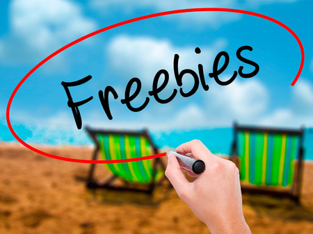 Man Hand writing Freebies with black marker on visual screen. Isolated on sunbed on the beach. Business, technology, internet concept. Stock Photo