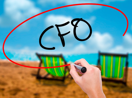 cfo: Man Hand writing CFO (Chief Financial Officer) with black marker on visual screen. Isolated on sunbed on the beach. Business, technology, internet concept. Stock Photo Stock Photo