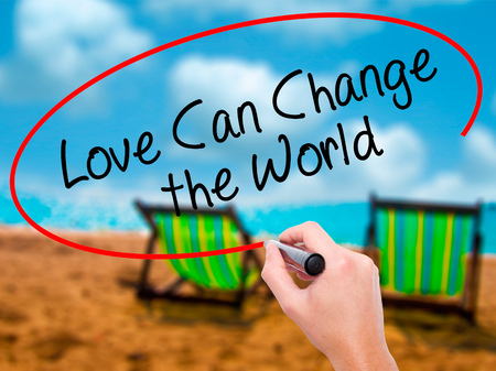 Man Hand writing Love Can Change the World with black marker on visual screen. Isolated on sunbed on the beach. Business, technology, internet concept. Stock Photo Stock Photo