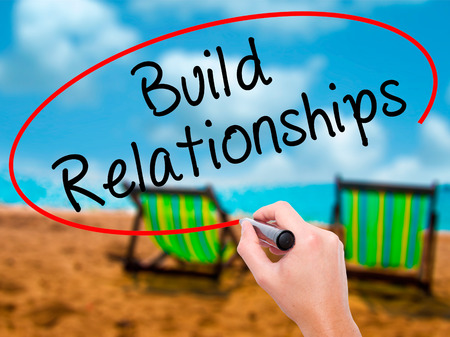 Man Hand writing Build Relationships with black marker on visual screen. Isolated on sunbed on the beach. Business, technology, internet concept. Stock Image Stock Photo