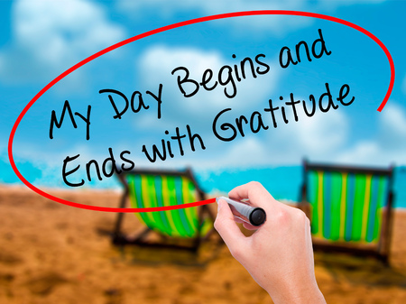 Man Hand writing My Day Begins and Ends with Gratitude with black marker on visual screen. Isolated on sunbed on the beach. Business, technology, internet concept. Stock Photo
