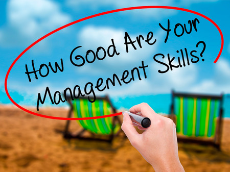 Man Hand writing How Good Are Your Management Skills? with black marker on visual screen. Isolated on sunbed on the beach. Business, technology, internet concept. Stock Photo
