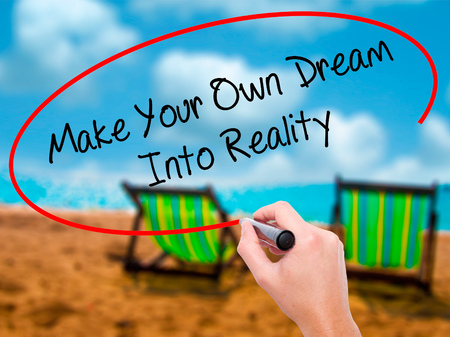 Man Hand writing Make Your Own Dream Into Reality with black marker on visual screen. Isolated on sunbed on the beach. Business, technology, internet concept.