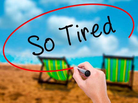Man Hand writing So Tired with black marker on visual screen. Isolated on sunbed on the beach. Business, technology, internet concept. Stock Image