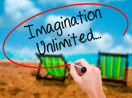 Man Hand writing Imagination Unlimited... with black marker on visual screen. Isolated on sunbed on the beach. Business, technology, internet concept. Stock Photo