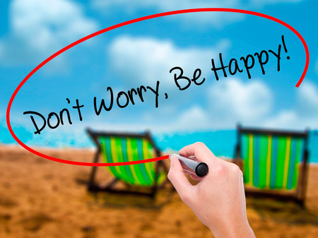 Man Hand writing Dont Worry, Be Happy! with black marker on visual screen. Isolated on sunbed on the beach. Business, technology, internet concept. Stock Photo