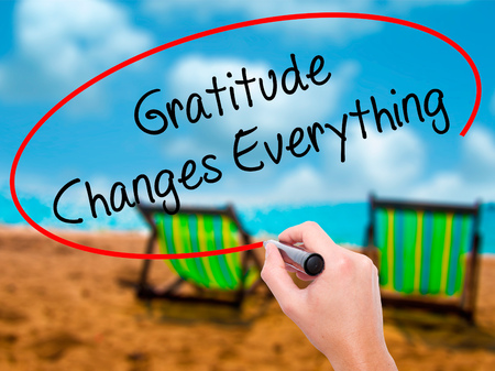 humility: Man Hand writing Gratitude Changes Everything with black marker on visual screen. Isolated on sunbed on the beach. Business, technology, internet concept. Stock Photo