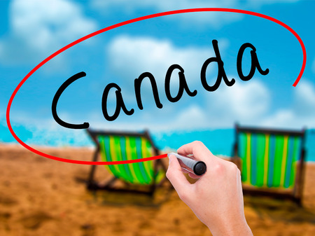 Man Hand writing Canada with black marker on visual screen. Isolated on sunbed on the beach. Life, technology, internet concept. Stock Image