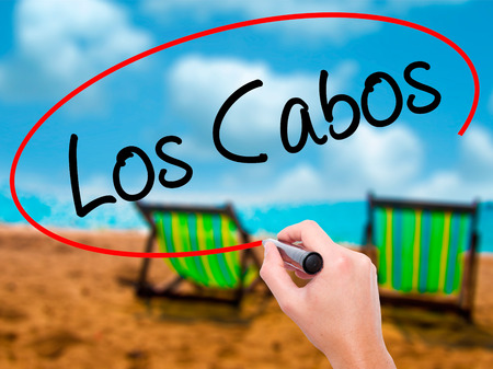 Man Hand writing Los Cabos with black marker on visual screen. Isolated on sunbed on the beach. Business, technology, internet concept. Stock Photo Stock Photo