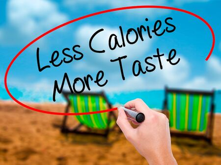 Man Hand writing Less Calories More Taste with black marker on visual screen. Isolated on sunbed on the beach. Business, technology, internet concept. Stock Photo Stock Photo