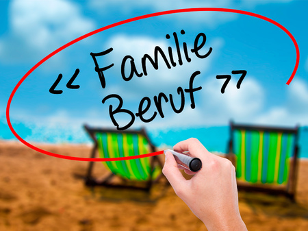 Man Hand writing familie beruf (Family Occupation in German) with black marker on visual screen. Isolated on sunbed on the beach. Business, technology, internet concept. Stock Photo
