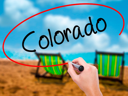 Man Hand writing Colorado  with black marker on visual screen. Isolated on sunbed on the beach. Business, technology, internet concept. Stock Photo