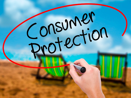 Man Hand writing Consumer Protection  with black marker on visual screen. Isolated on sunbed on the beach. Business, technology, internet concept. Stock Photo