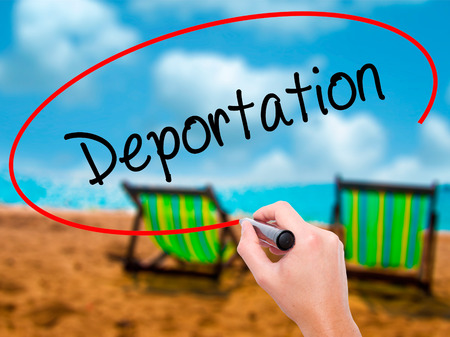 naturalization: Man Hand writing Deportation  with black marker on visual screen. Isolated on sunbed on the beach. Business, technology, internet concept. Stock Photo