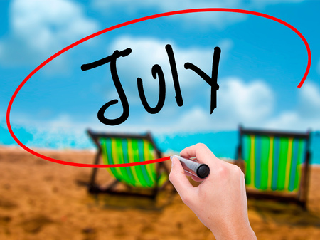 Man Hand writing July with black marker on visual screen. Isolated on sunbed on the beach. Business, technology, internet concept. Stock Photo