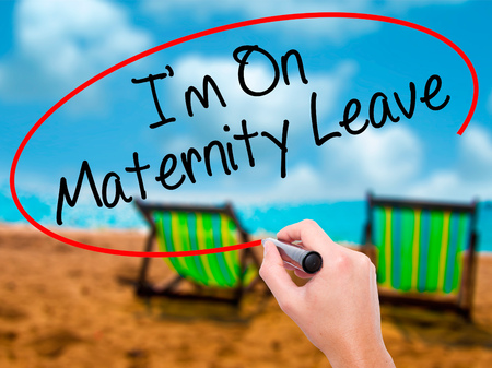 Man Hand writing  Im On Maternity Leave with black marker on visual screen. Isolated on sunbed on the beach. Business, technology, internet concept. Stock Photo