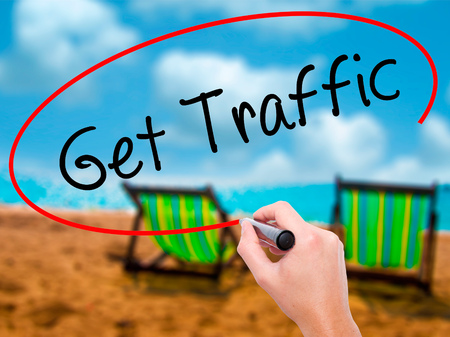 pageviews: Man Hand writing Get Traffic with black marker on visual screen. Isolated on sunbed on the beach. Business, technology, internet concept. Stock Photo