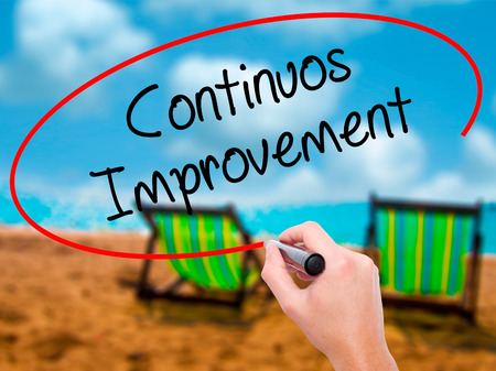 Man Hand writing Continuos Improvement with black marker on visual screen. Isolated on sunbed on the beach. Business, technology, internet concept. Stock Photo