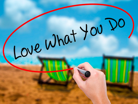 Man Hand writing Love What You Do with black marker on visual screen. Isolated on sunbed on the beach. Business, technology, internet concept. Stock Photo
