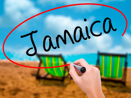Man Hand writing Jamaica  with black marker on visual screen. Isolated on sunbed on the beach. Business, technology, internet concept. Stock Photo Stock Photo
